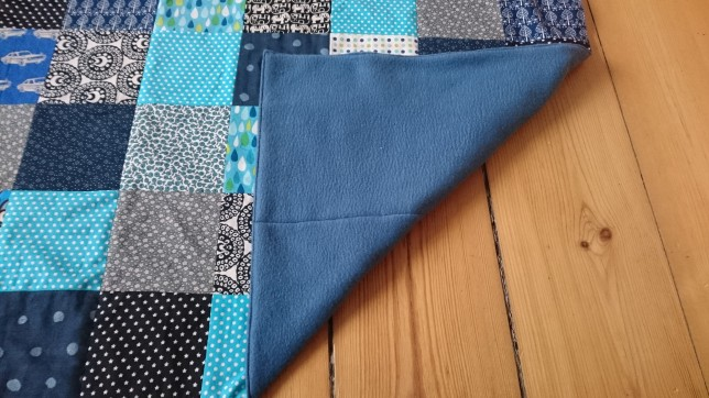 Patchwork tæppe blåt bagside foldet op